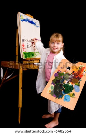 Barefoot little girl busily painting on an easel.  Isolated on black.
