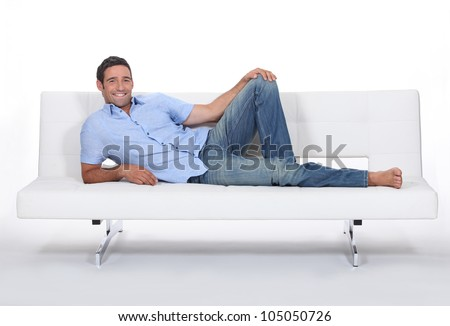 Barefoot man lying on a couch