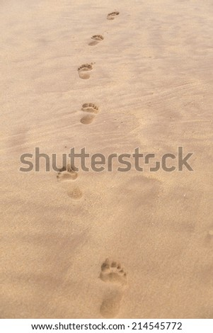 Barefoot prints on sandy beach - stock photo