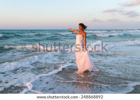 Barefoot young bride in a partially wet  wedding dress, enjoys walking in the water on a sandy beach in late summer, at dusk.