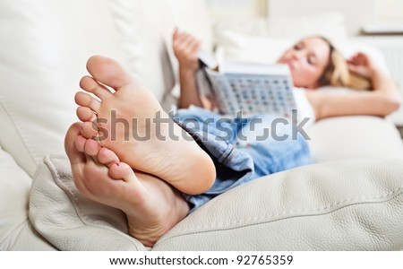 Barefoot young woman lying on sofa and reading book, shallow depth of field, focus on foot soles - stock photo