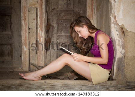 Barefoot young woman reading a book on an old derelict porch