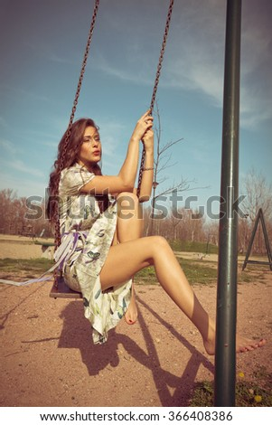 barefoot young woman sit on swing in summer dress  full body shot, wind in hair, retro colors  - stock photo