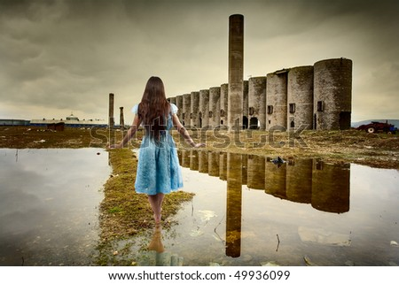 Barefoot young woman walking in a deserted industrial landscape - stock photo