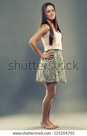 barefooted pretty brunette teenager wearing a summer dress - stock photo