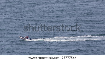 BARFLEUR, FRANCE - JULY 01: Two men enjoying ride with speedboat on the English Channel near Barfleur, France on July 1, 2011. Hidden cliffs make this part of the Atlantic ocean dangerous. - stock photo