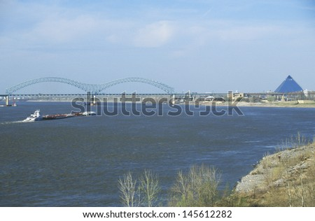 Barge on Mississippi River with Hernando de Soto Bridge and Memphis, TN - stock photo