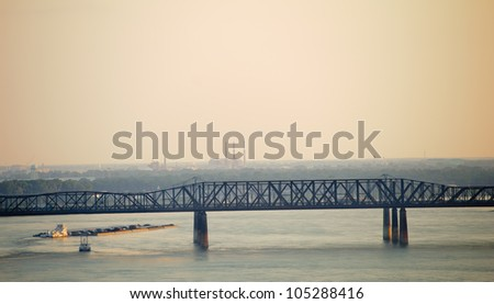 Barge traveling down the Mississippi River under the Harahan Bridge at Memphis, Tennessee. - stock photo