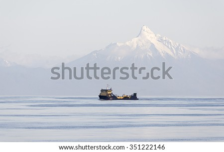 barge with mountain with snow in the background, south America Chile, travel to CHILE, cruise in CHILE, Patagonia region of CHILE - stock photo