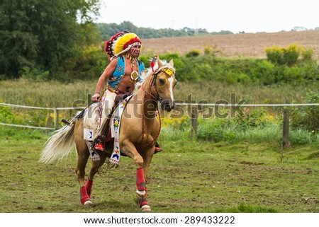Barglowka, Poland - September 26, 2012: A man dressed as Indian chief with head-dress rides a horse during an event in Barglowka, Poland - stock photo