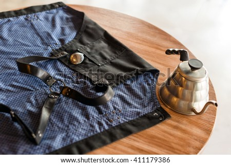 Barista apron on the table in cafe waiting for its owner. Product photography. Coffee preparation service concept. Selective focus