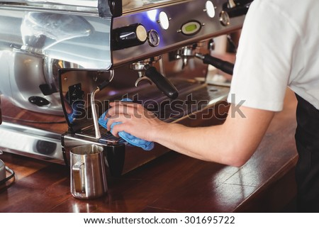 Barista cleaning coffee machine at coffee shop - stock photo