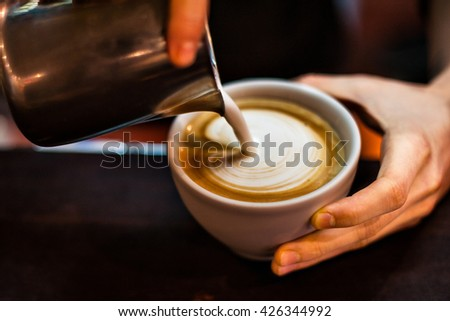 Barista creating latte art on long coffee with milk.  - stock photo