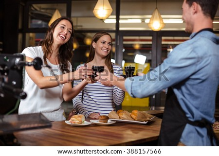 Barista giving coffees to smiling women at the bar