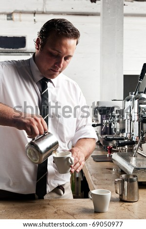 Barista heats milk and pours it for his cappucino - stock photo
