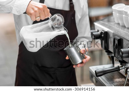 Barista pouring milk from big transparent jar to the metal milk pitcher - stock photo