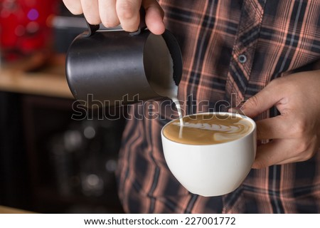Barista pouring milk in capuccino coffee in coffeeshop - stock photo