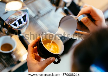Barista pouring milk into art cappuccino or latte at coffee shop - stock photo
