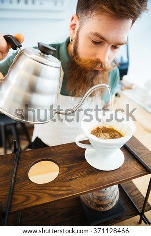 Barista pouring water on coffee ground with filter in coffee shop