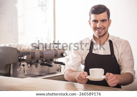 Barista prepares cappuccino in his coffee shop. - stock photo