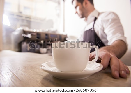 Barista prepares cappuccino in his coffee shop. Close-up cup of coffee. - stock photo