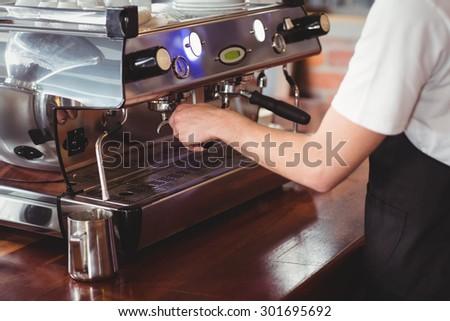 Barista preparing coffee machine at coffee shop - stock photo