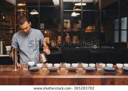 Barista preparing coffee tasting with rows of cups and beans - stock photo