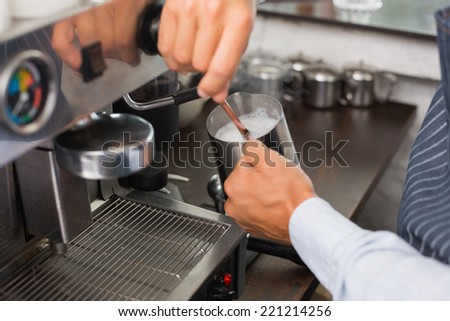 Barista steaming milk at the coffee machine at the coffee shop - stock photo