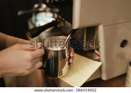 Barista steaming milk in cafe - stock photo