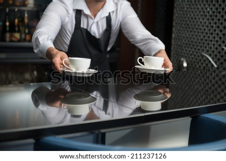 Barista wearing white shirt and black apron standing at the bar counter suggested us to taste his coffee - stock photo