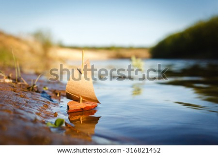 Bark Toy Boat on river at sunset - stock photo