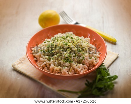 barley risotto with lemon peel and pepper, selective focus - stock photo