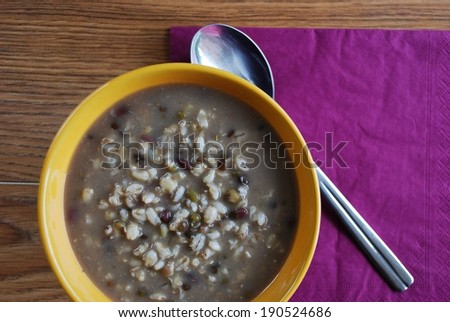 Barley soup with mixed beans flavored with miso in an orange bowl