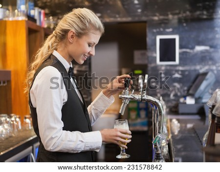 Barmaid pulling a glass of beer in a bar - stock photo