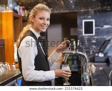 Barmaid pulling a glass of beer while looking at camera in a bar - stock photo