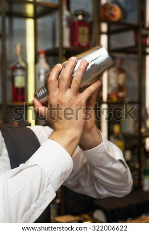 Barman at work, preparing cocktails. Shaking cocktail shaker. concept about service and beverages. - stock photo