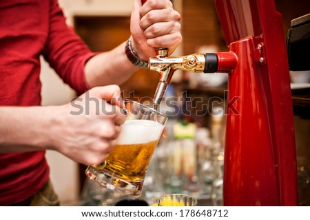 Barman brewing a draft, unfiltered beer at pub or bar - stock photo