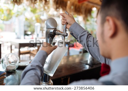 Barman filling mug with draft beer, view over the shoulder - stock photo