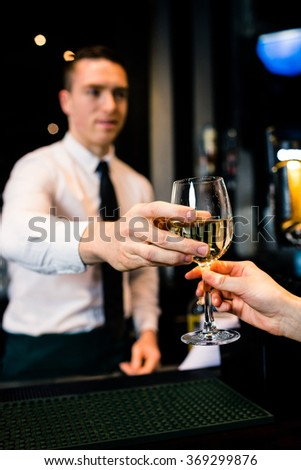Barman giving a drink to customer in a bar - stock photo