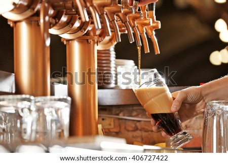 Barman hand pouring a lager beer in a glass. - stock photo