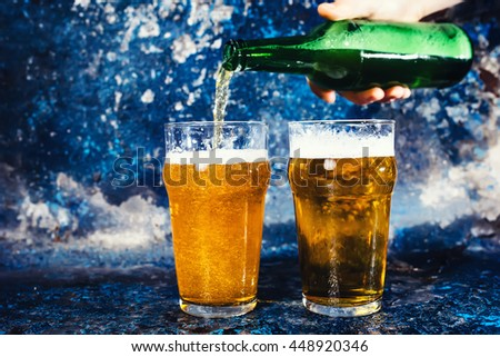 barman hand with beer bottle pouring a draught lager beer - stock photo