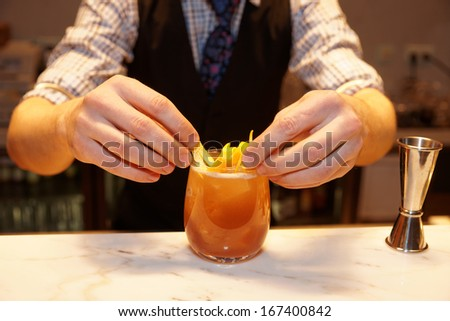 Barman is decorating cocktail with lemon zest  - stock photo
