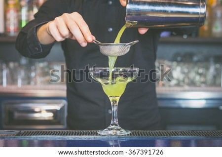 Barman is pouring alchool into the glass - drink, people, lifestyle and nightlife concept - stock photo