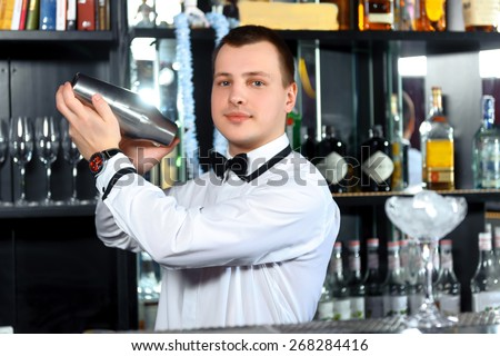 Barman job. Young handsome barman mixing cocktails in shaker at the bar - stock photo