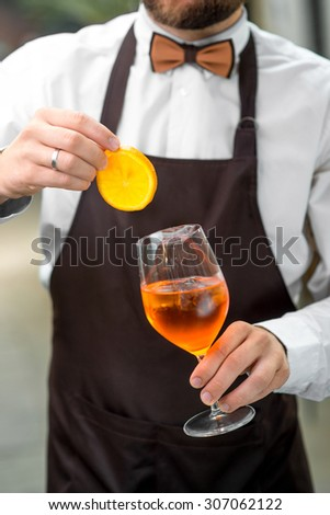 Barman making cocktail with sparkling wine, Aperol and orange. Close up view focused on hands - stock photo