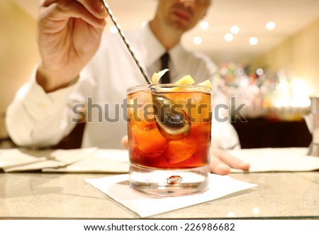 barman mixing a cocktail against bar background - stock photo