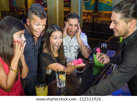 Barman performing magic Trick to surprised Guests - stock photo