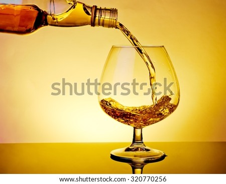 barman pouring snifter of brandy in elegant typical cognac glass on table on warm atmosphere - stock photo