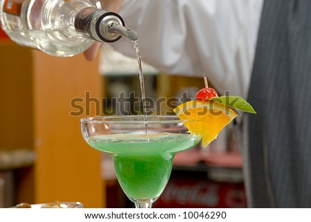 barman pouring tequila on a drink - stock photo