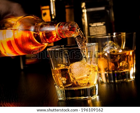 barman pouring whiskey in front of whiskey glass and bottles on wood table - stock photo